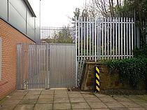 2400mm high galvanised steel palisade fencing and access gate. Pales are closed spaced to prevent access to the emergency gate release lock. A small quadrant has been secured where the fence steps in height.